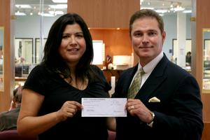 Marisa Diamond, a Jewlery Exchange customer, receives a $5000<br>check from Ernie Cara of the Seiko Watch Corporation.