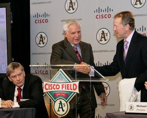 Oakland Athletics (A's) Owner and Managing Partner Lew Wolff,<br>standing left, and Cisco President and CEO John Chambers,<br>right, unveil the 'Cisco Field' logo, while Major League<br>Baseball Commissioner Bud Selig sits, left, at an event<br>Tuesday at Cisco headquarters in San Jose, Calif., to announce<br>an agreement to build a baseball park in Fremont, Calif.,<br>to serve as the new home of the A's.<br>Cisco photo by Scott Griggs.