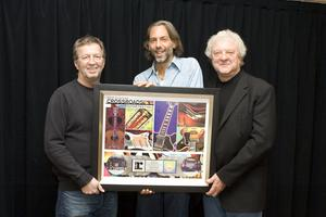 Eric Clapton receives a plaque to commemorate the Crossroads Guitar<br> Festival DVD achieving the 8x Platinum mark. Pictured left to<br> right are Eric Clapton, Crossroads Guitar Festival Founder, along with<br> Scooter Weintraub and Peter Jackson, Festival Co-Producers<br> and Crossroads Centre Board Members.