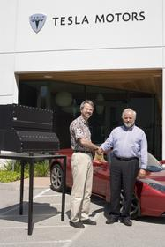 Martin Eberhard, Tesla CEO (left) and Jan-Olaf Willums, Think CEO (right) with Tesla's Energy Storage System (ESS) and the Tesla Roadster.