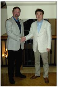 Bruce L Block and Hiroyoshi Miyama shake hands at the signing of joint venture agreement