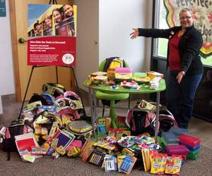 Proud TopLine employee Amy Eder with more than 400 school supply donations from TopLine employees and members.