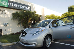 A Nissan LEAF electric vehicle (EV) gets a charge at a charging station outside of an Enterprise Rent-A-Car office in Carson, Calif.  Enterprise Rent-A-Car acquired a 'test' LEAF from Nissan that it will use to help educate customers and employees about EV rentals and infrastructure before the company takes its first batch of fleet EVs in December.