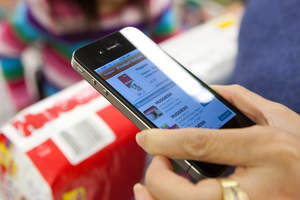Consumer saving money using Pushpins mobile coupons at a grocery store.