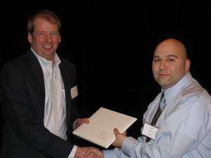 TJ Briones (right), TRC Safety Steward, accepts the ExxonMobil Environmental Services Global Safety Recognition Certificate from Andrew Wescoat (left), Manager, ExxonMobil Environmental Services Company.