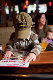 A child reviews the menu at Applebee's, which on Veterans Day will provide free Thank You meals to veterans and active duty military.