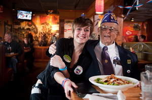 A team member and a veteran share a smile at Applebee's on Veterans Day, where veterans and active duty military receive a free Thank You meal.