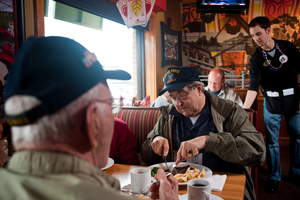A veteran enjoys a free Thank You meal with fellow veterans on Veterans Day at Applebee's.