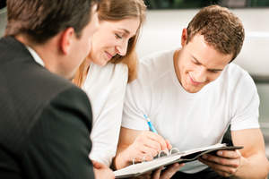 Couple signing sales contract at car dealership