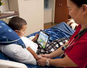 A young patient visiting GetWell Town, the GetWellNetwork interactive patient care solution on an iPad.