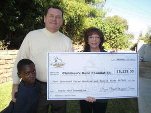 Adolf Baguma, a child burn survivor from Uganda, helps accept the check donation from Dryer Vent Wizard to the Children's Burn Foundation with the Foundation's Board Chairman Doug Mancino and Executive Director Carol Horvitz.