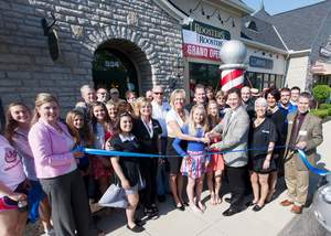 Roosters MGC owners Lisa Groome and Tom Quick, at center, prepare to cut the ribbon with their two daughters at the store's grand opening celebration in Westerville.