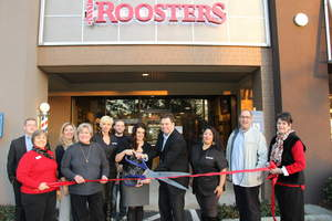 Renee and Ross Christen, owners of Roosters Men's Grooming Center in Atlanta, prepare to cut the ribbon for their new store with assistance from Roosters' team and representatives from the Sandy Springs/Perimeter Chamber of Commerce.