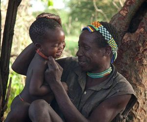 Photo:  Courtesy of Benenson Productions Hadza man and baby in Rift Valley of Tanzania