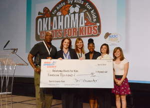 The membership of the National Association of Sports Commissions donated $14,000 to Oklahoma Cleats for Kids at their annual symposium held last week. Pictured here (L to R) are NASC Board Chair Kevin Smith with Stacy McDaniel of Cleats for Kids and youth beneficiaries of the program.