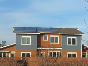 Ground view of rooftop solar installations on two Great Oak condominiums