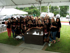 Employees at Saia's Houma, La. office pose for a group photo with the time capsule the company buried this week.