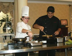 Celebrity Chef Jose Santaella and Chef Nicole Hassen prepare tostones for residents in the Oakwood Common dining room.