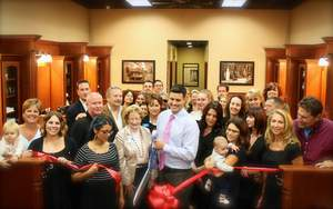 David Graves, III, of Roosters Men's Grooming Center, cuts the official ribbon during the store's grand opening in Carlsbad.