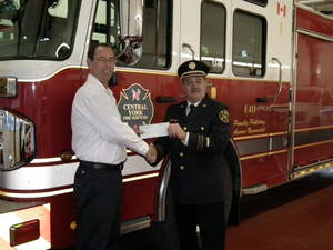 Chief of Prevention Les Chaisson of Central York Fire Services in Ontario accepts the DVW grant from Canadian franchisee Tyler Johnson.