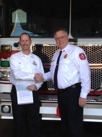 DVW franchisee Joe Enzenberger makes a grant presentation to Steve Engledow, Chief of the New Lenox Fire Protection District.