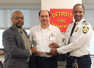 Detroit Executive Fire Commissioner Edsel Jenkins, at left, and Chief Dale Bradley accept educational grant funds from DVW franchisee Larry Butterfield, at center.
