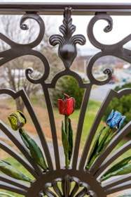 hand forged railings and juliet balcony, custom painted multi color tulip design.