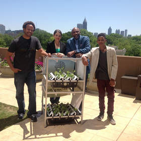 Ready to demonstrate Acopia Harvest's Green Machine are, left-to-right, Todd Mitchell, Seeds Global(Atlanta School Dept. Initiative); Amy Chauvin, Research Director, Acopia Harvest; Dr. Gerald Austin, Community Developer; Gerald Austin III, Student, Birmingham, AL