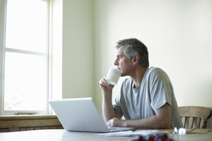 man staring out window holding mug in front of laptop computer
