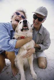 Couple hugging a dog.
