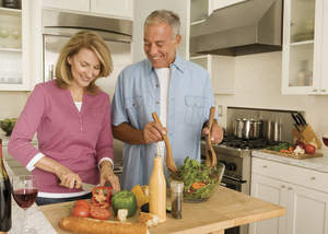 Man and woman cutting up vegetables