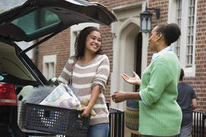 Mother and daughter talking while loading the car for college.