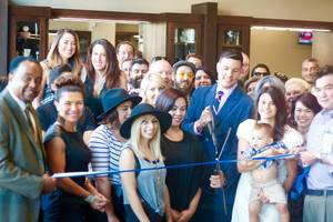 Store owner David Graves, III, center prepares to cut the official ribbon for Roosters Men's Grooming Center in San Diego's East Village.