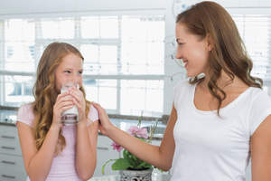 Mom and daughter in kitchen drinking milk