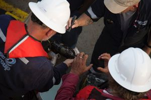 Endurance Exploration Group and Eclipse Group crewmen investigate a bottle recovered from the wreck of Steamship Connaught.