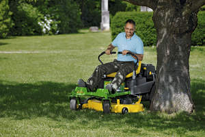 Man mowing his lawn on a John Deere riding lawn mower.