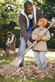Father and son raking leaves.
