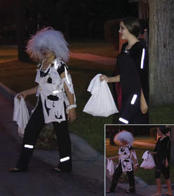 Children in costumes wearing reflective gear while out at night.