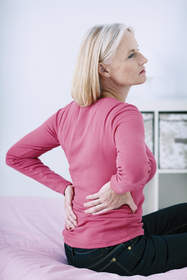 Woman sitting on bed holding her back.