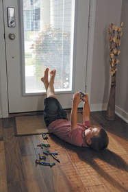 Boy playing with toy while lying on the floor next to a door.