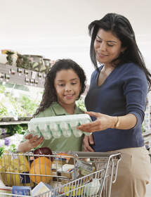 Mother and daughter grocery shopping for eggs.