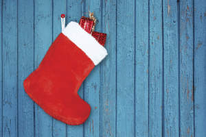 Red Christmas stocking on blue wall.