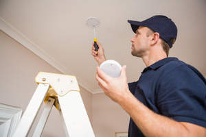 Man installing a carbon monoxide detector in ceiling.