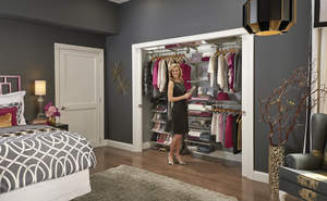 Woman standing in front of organized closet.