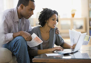 Man and woman going over paperwork with a laptop