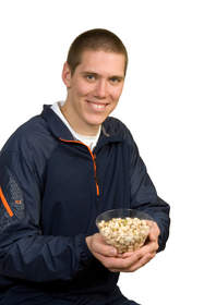 Man holding bowl of pistachios.