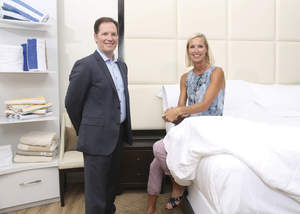 Man and woman displaying luxurious bedding.
