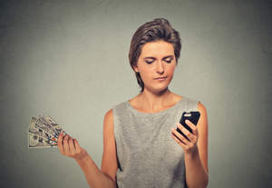 Woman holding money in one hand and using her cell phone in the other hand.