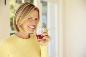 Woman drinking Sunsweet prune juice.