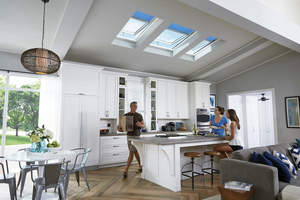 Man, woman and teenager in kitchen under Velux skylights.